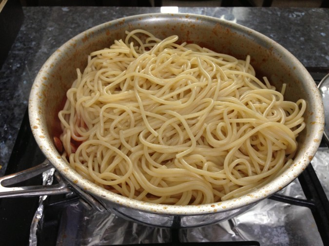 adding spaghetti noodles to sauce